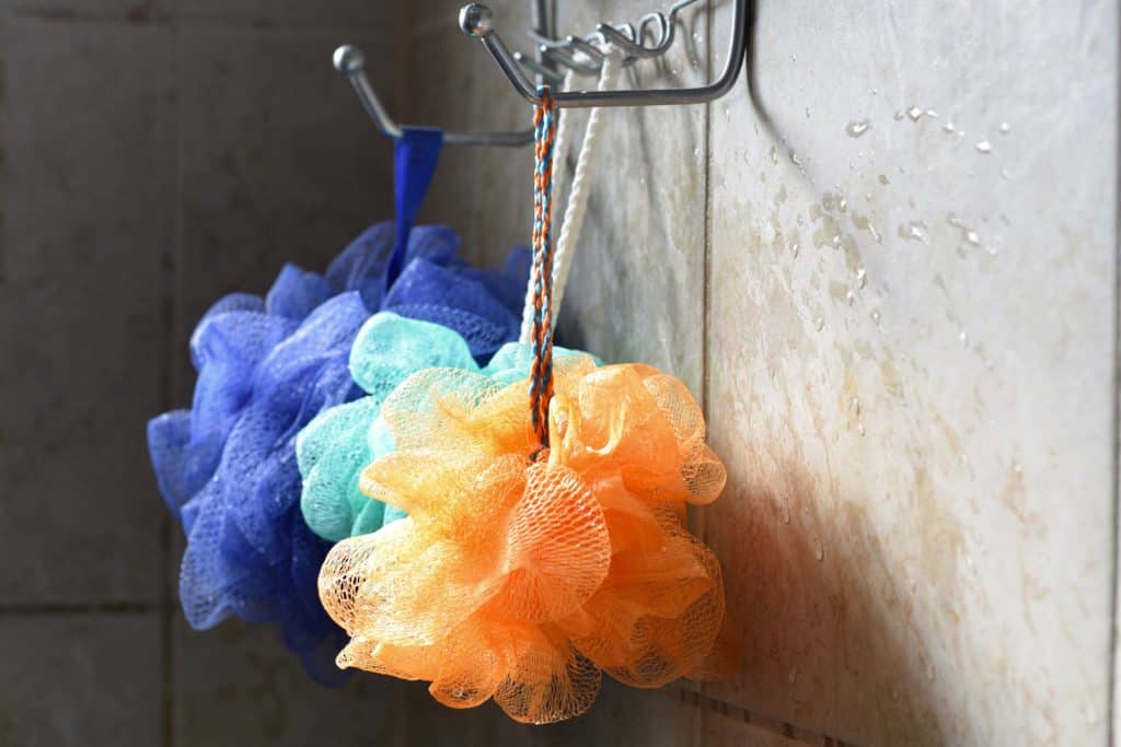 Light catches loofahs hanging from a rack