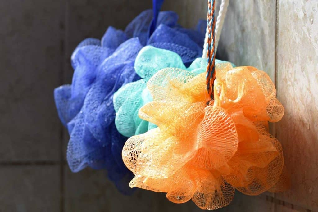 Light catches loofahs hanging from a rack, How To Clean A Mesh Loofah - A Look At Various Methods