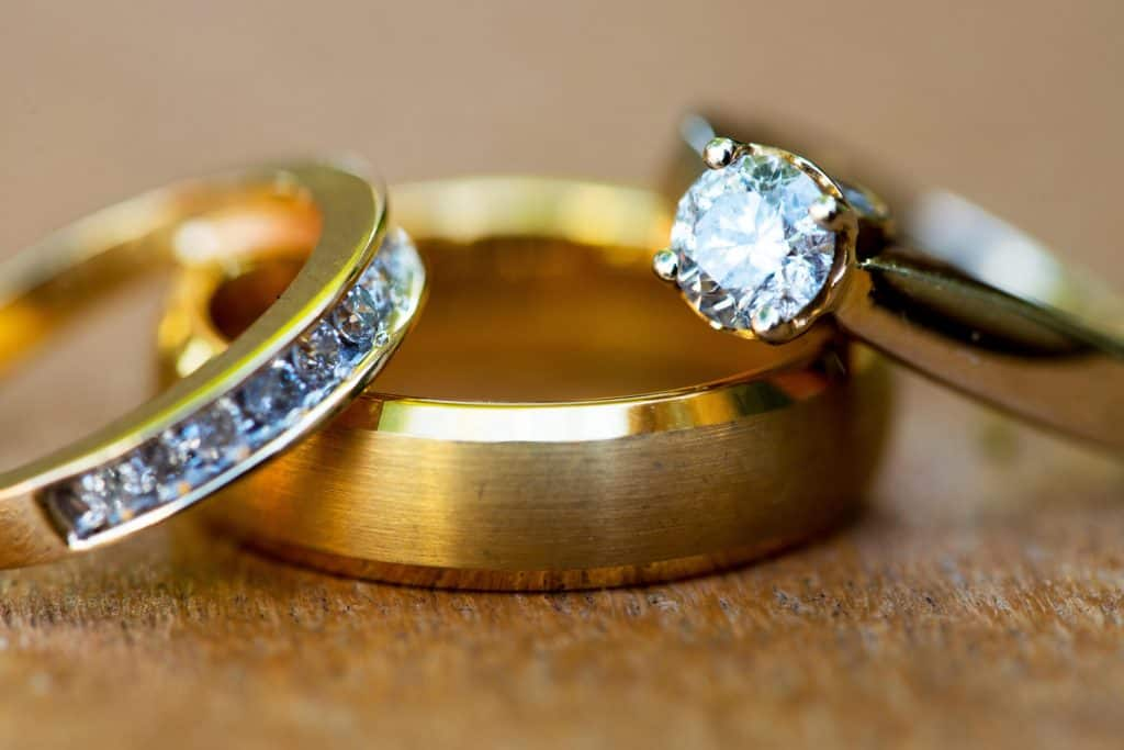 Macro photo of bride and groom's gold wedding rings captured in natural light