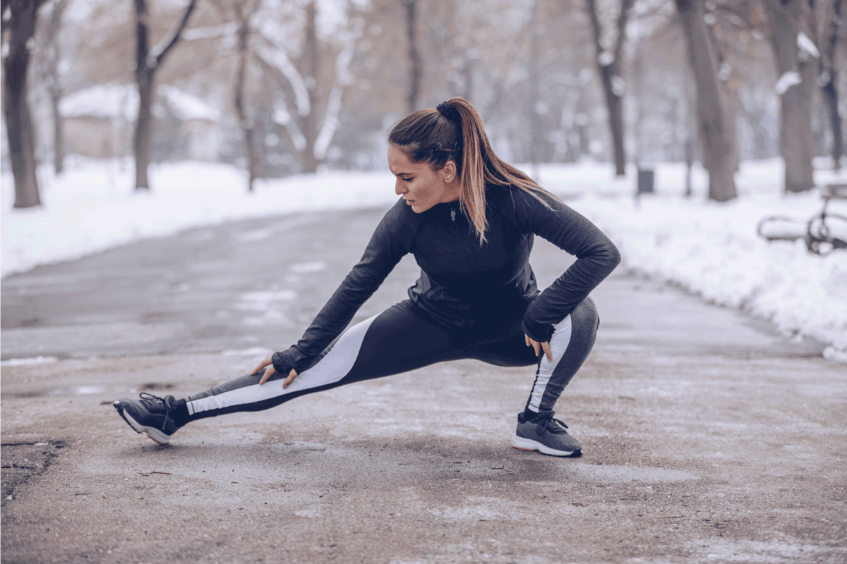 One woman, young fit girl training on a cold winter day outdoors wearing yoga class