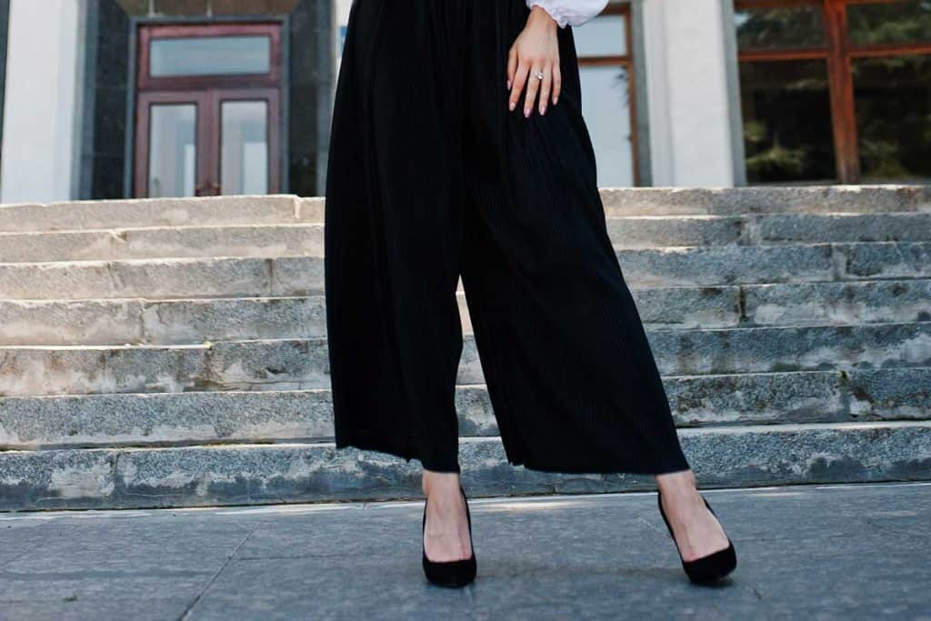 Fabulous woman in white blouse and broad black pants posing on the stairs, What Shoes To Wear With Palazzo Pants? [5 Great Options]