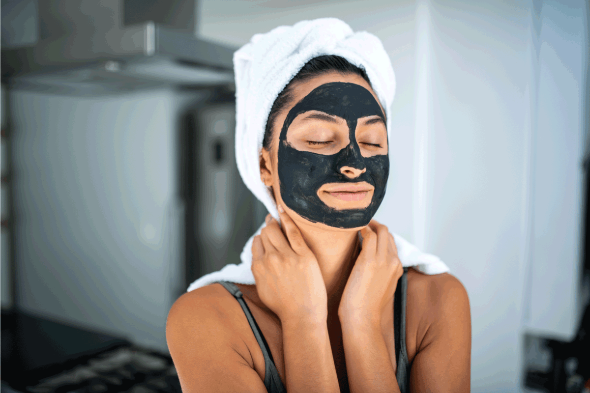 Portrait of a smiling Latin woman using beauty treatment at home . She have black facial mask and she has her eyes closed