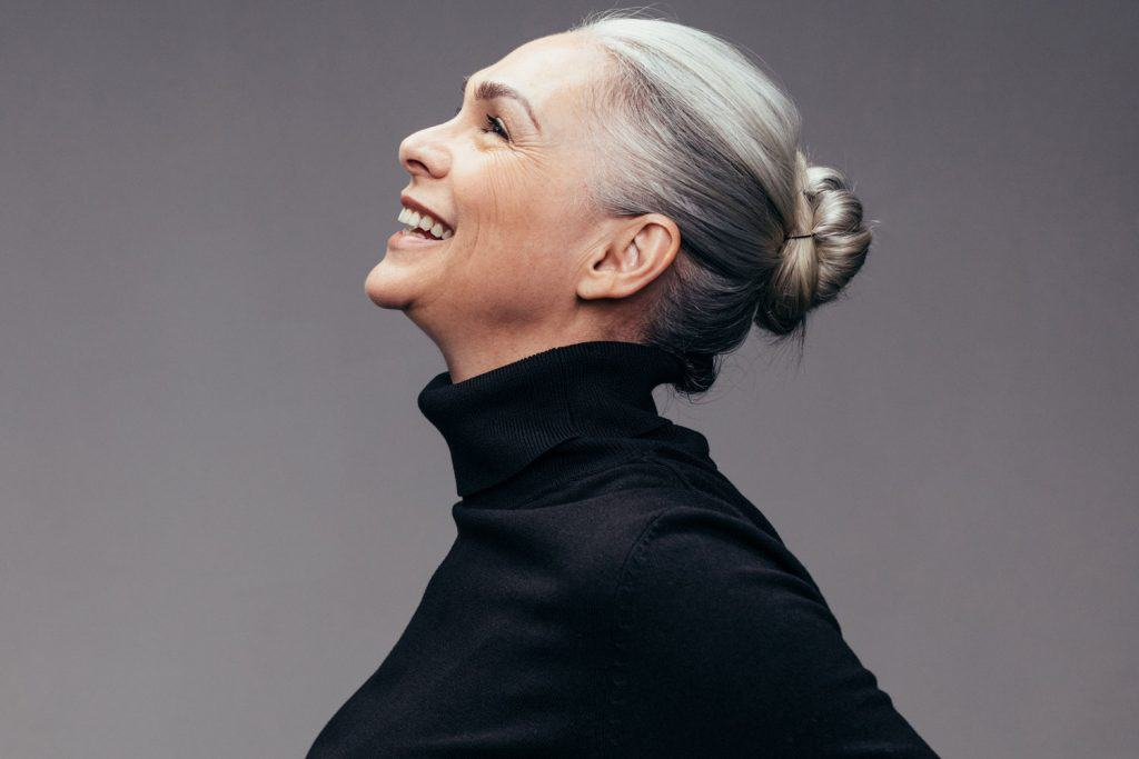 Side view of senior woman laughing on gray background. Profile view of mature woman in black casuals looking happy, Does Electrolysis Work On White Or Gray Hair?