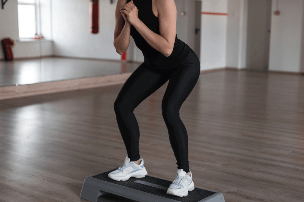Slim-sporty-young-woman-in-sporty-black-clothes-crouches-standing-on-the-platform-steps-in-the-gym.-How-To-Wear-Black-Leggings-[4-Outfits-To-Consider]