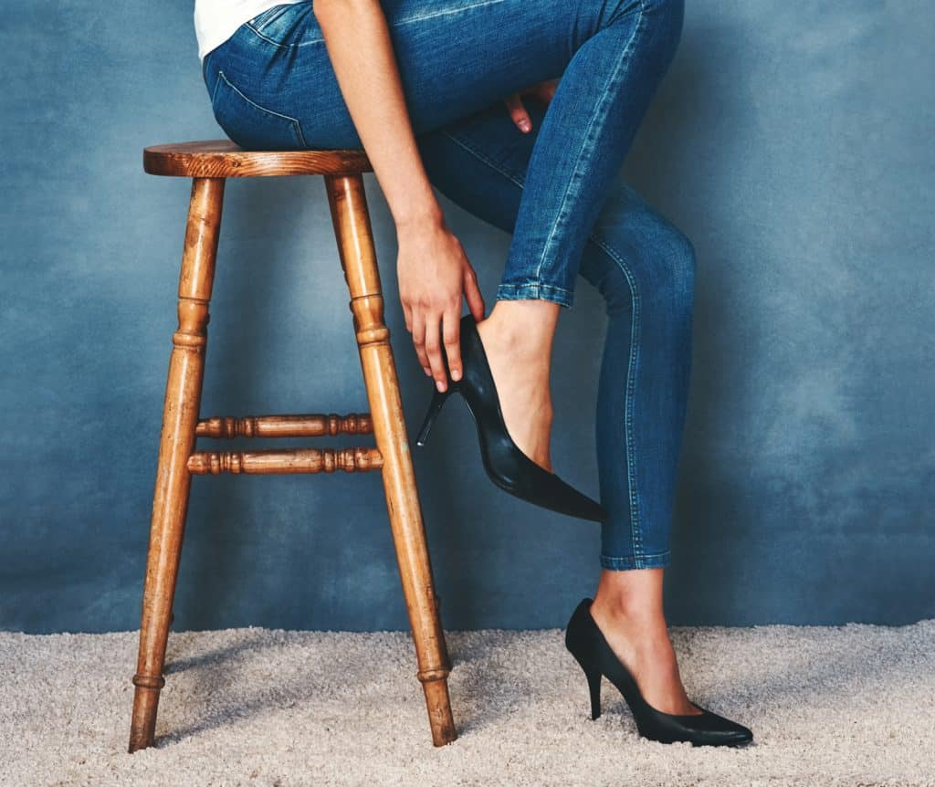 Studio shot of an unidentifiable young woman trying on a pair of high heels against a blue background