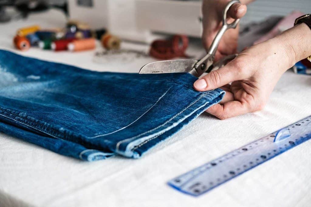 Tailor cutting jeans with scissors at workshop