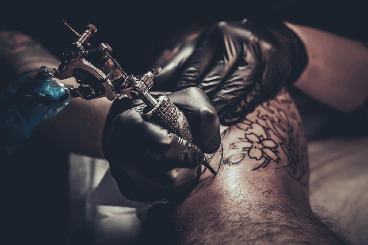 Tattoo master making tattoo on customer's leg
