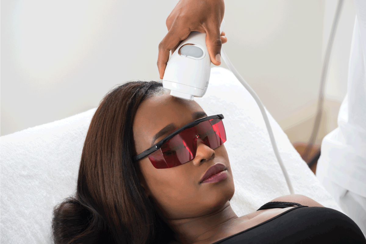 Therapist Giving Laser Epilation Treatment To Young African Woman