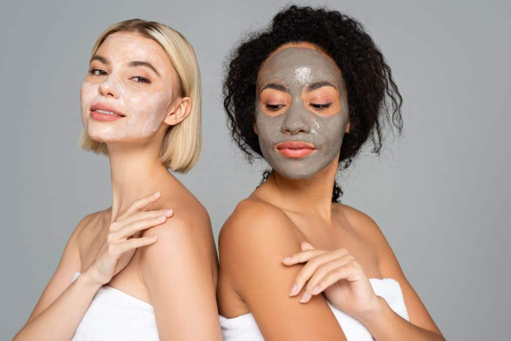Two women showing their clay mask on the Spa