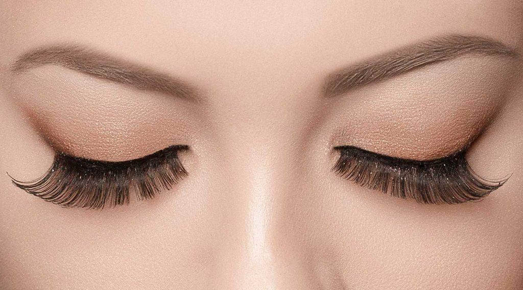Woman eyes with false eyelashes, black eyeliner and natural beige makeup