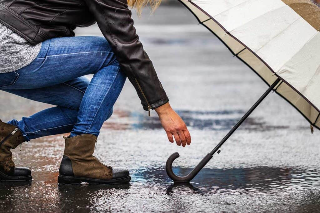 Woman in jeans and black leather jacket picking up umbrella on the street