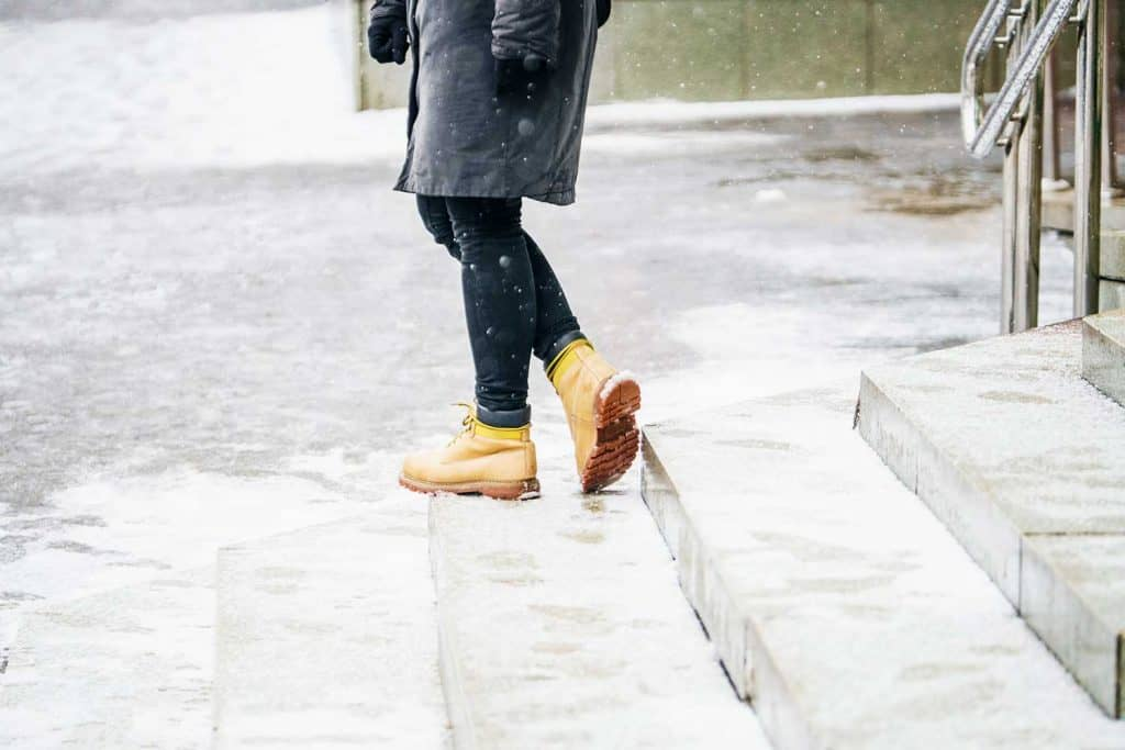Woman in yellow leather boots walking on snowy granite stairs