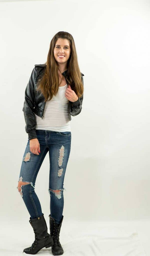 Woman smiling while standing in torn jeans and black leather jacket