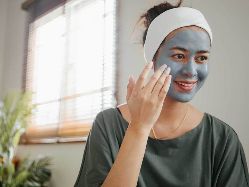 Woman with headband applying organic face scrub