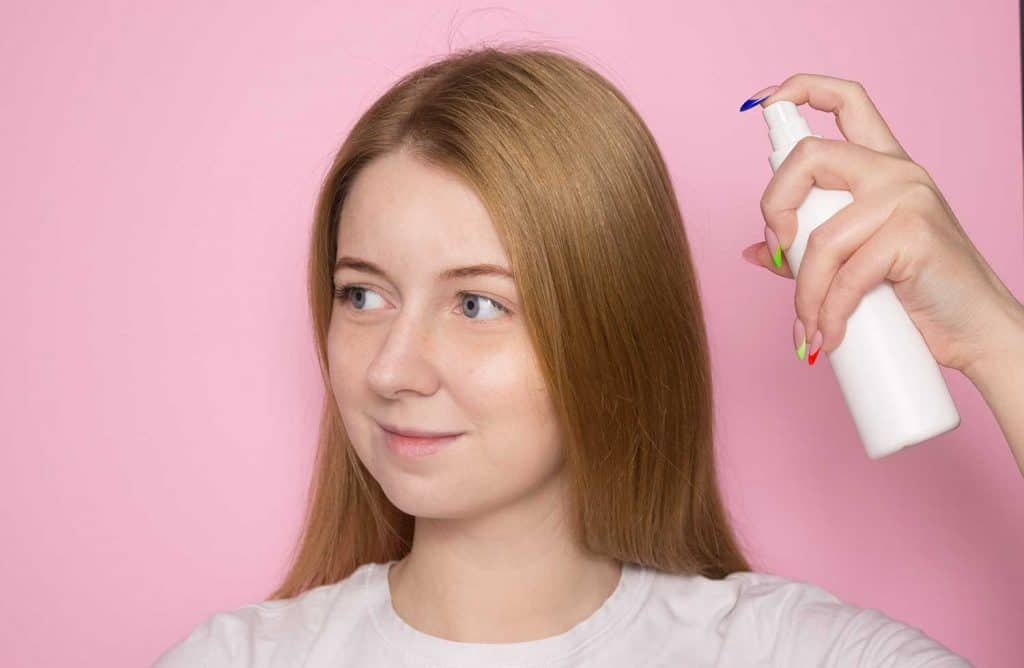 Woman with long hair holds a spray bottle in a white bottle and sprays it on her hair