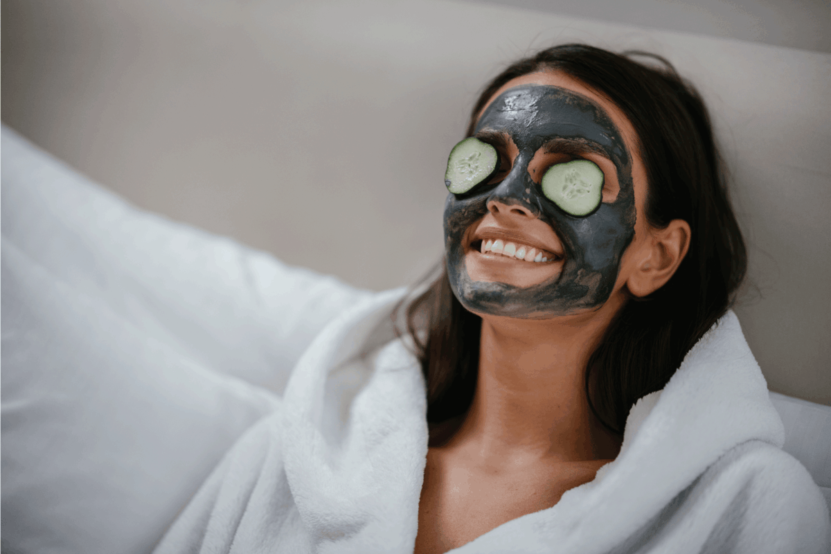 Woman with slices of cucumber on the eyes, clay mask on face