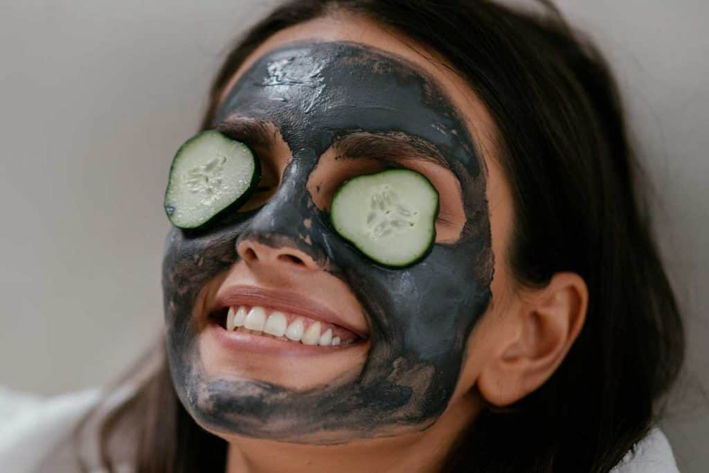 A women applying mud mask and cucumber on the face, Can I Use A Dead Sea Mud Mask Everyday?