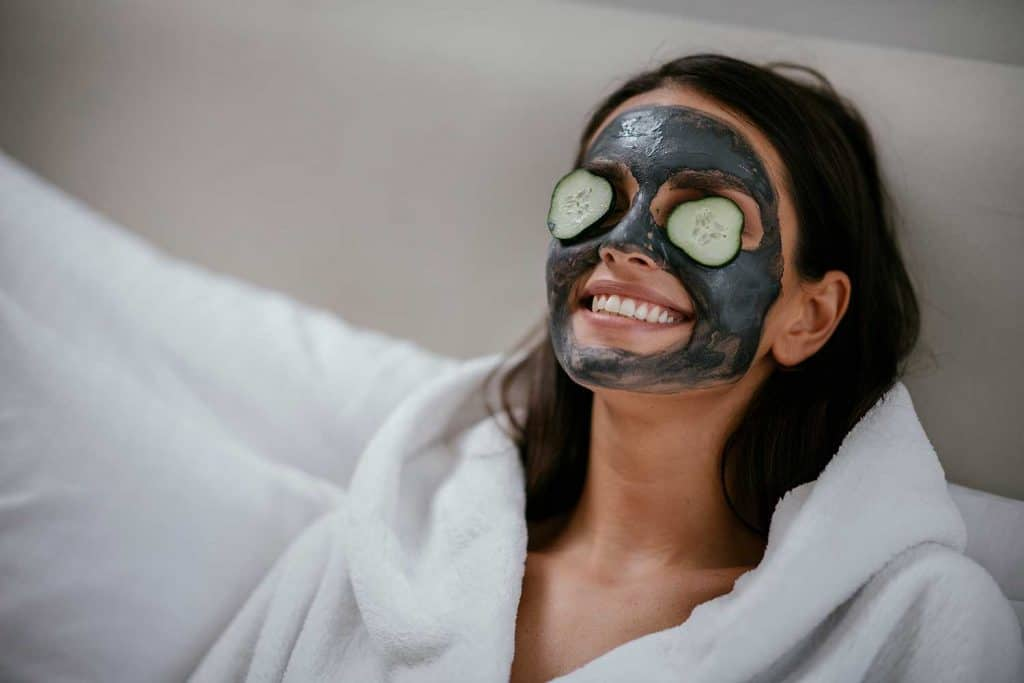 Women applying mud mask and cucumber on the face