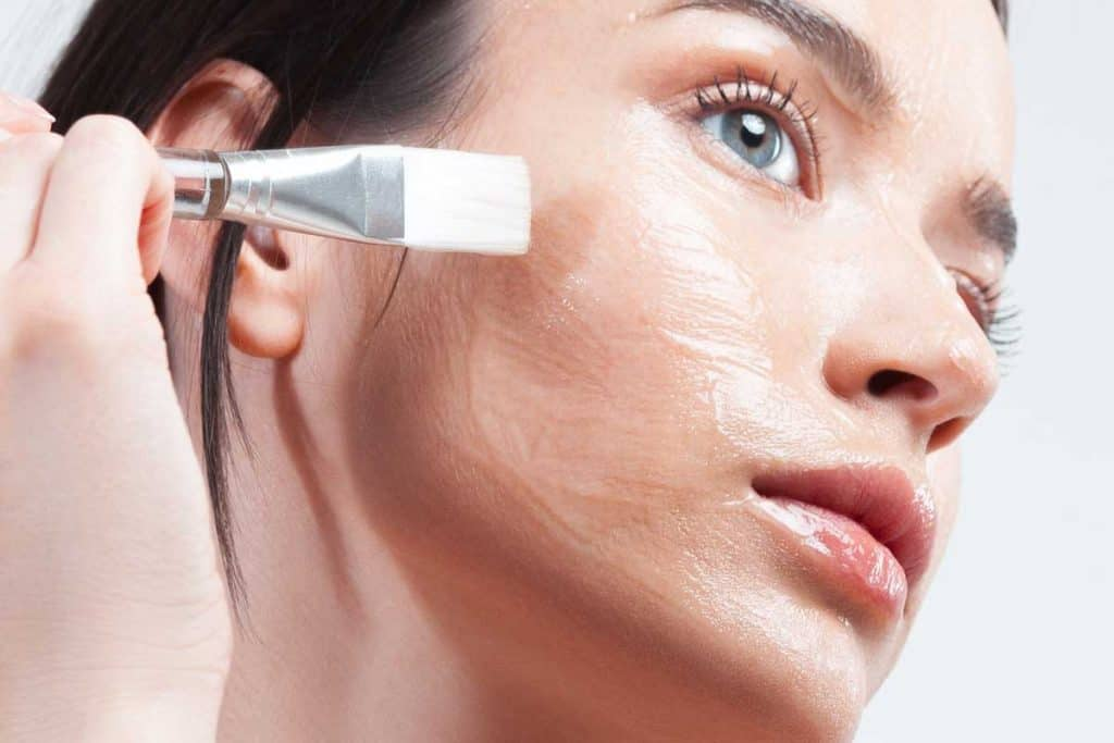 Young beautiful woman with clean perfect skin applies cosmetic brush with transparent moisturizing face mask, How To Remove A Gel Face Mask