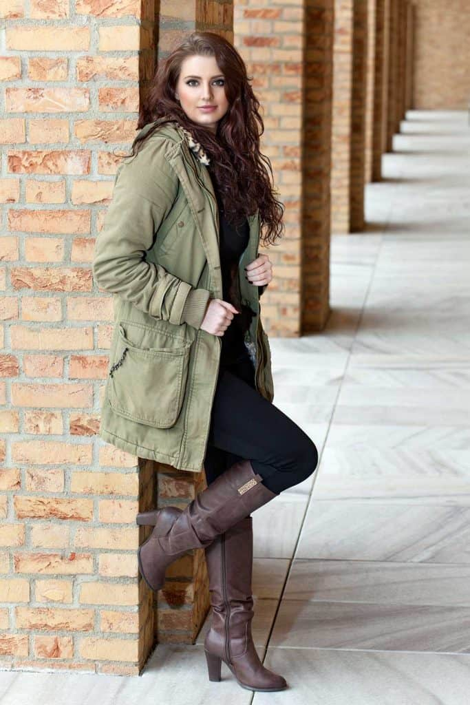 Young brunette in long warm jacket, leggings and high-heeled leather boots