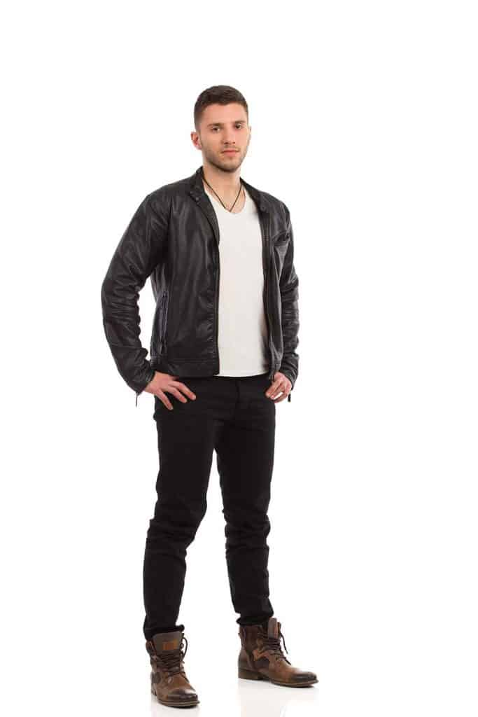 Young man in black leather jacket stands with hand on hip