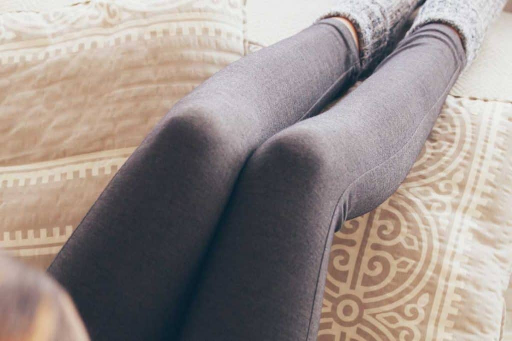 Young woman in leggings drinking coffee sitting on the sofa, How To Get Rid Of Pilling And Fuzzies On Leggings