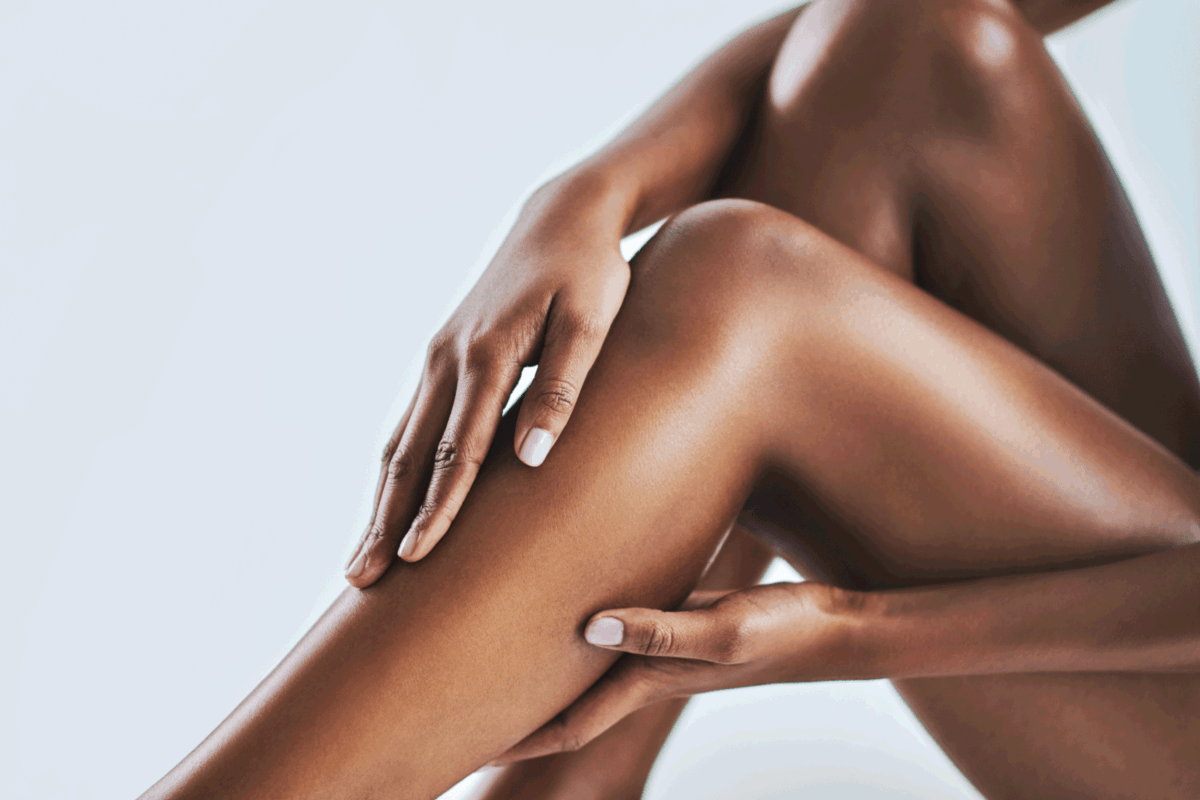 a young woman caressing her legs. Is Electrolysis Good For Dark Skin