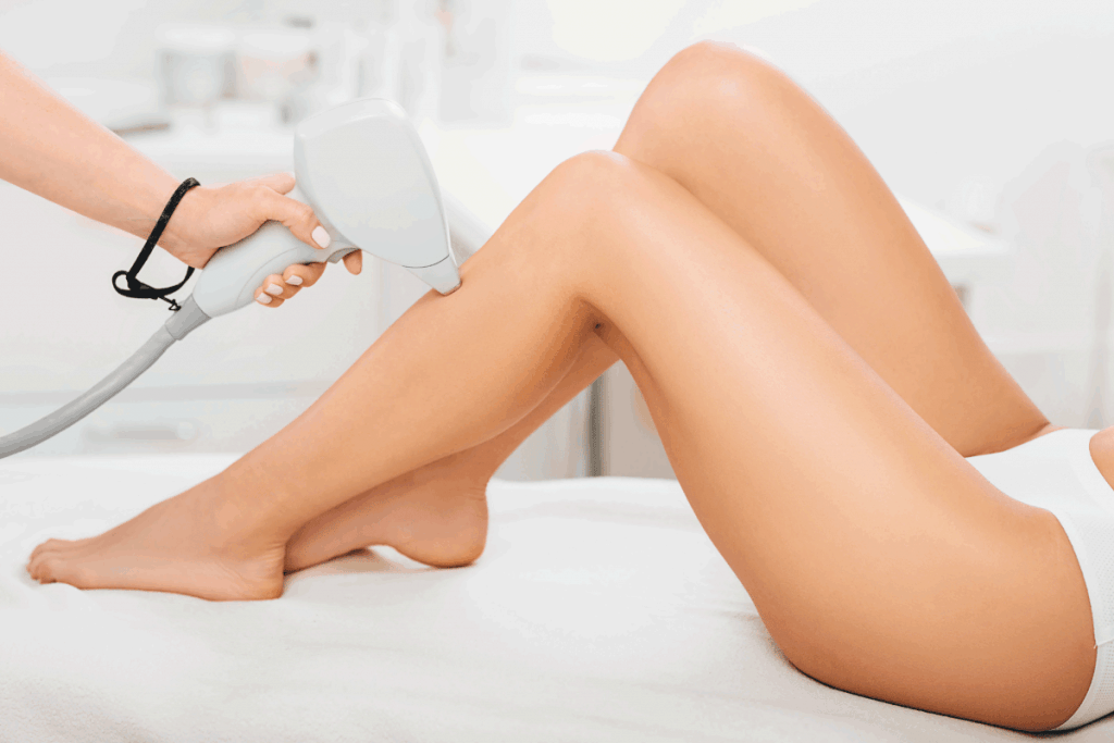 beautician removes hair on beautiful female legs using a laser. hair removal on the legs, laser procedure at clinic. Does Electrolysis Affect Tattoos