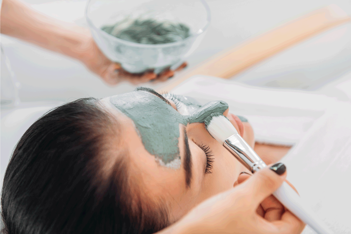 cosmetologist applying clay mask with brush on female face in spa salon. How Often Should You Use An Aztec Clay Mask