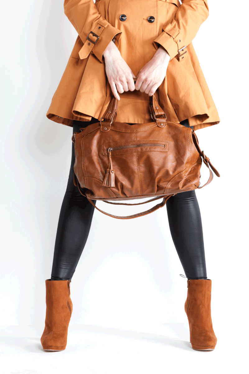 standing woman wearing coat and fashionable brown shoes with a handbag and black leggings