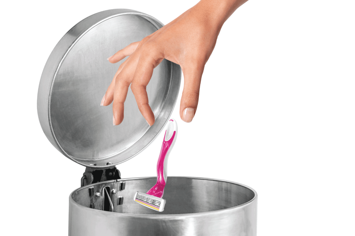 woman throwing shaving blade unto stainless steel trash can