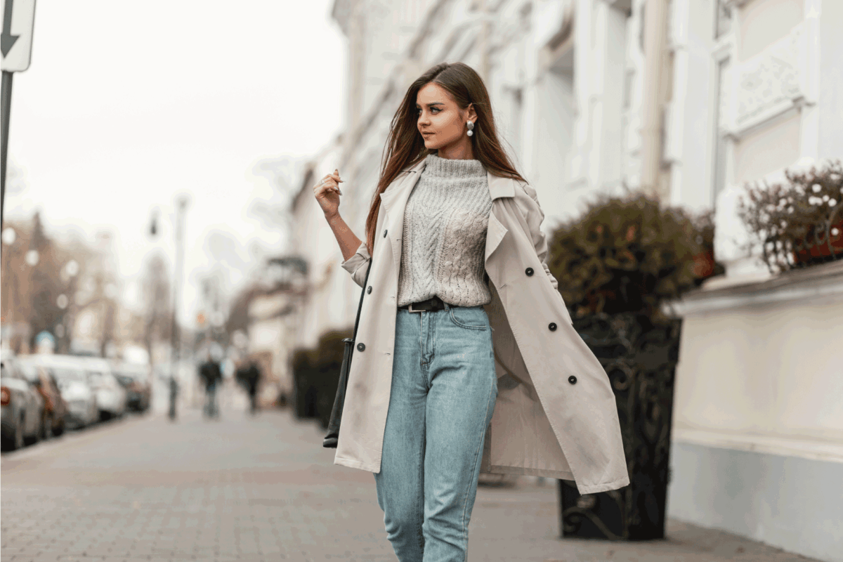 young beautiful woman in a fashion trench coat in a stylish knitted sweater with a leather black bag walks on the city near a white building