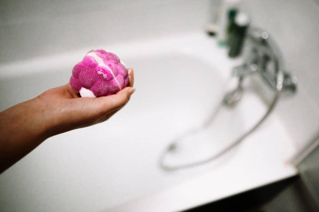 A bath bomb by a bathtub