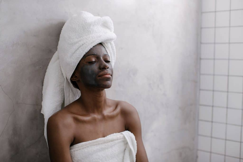 A beautiful woman with charcoal mask on her face resting in the sauna bath