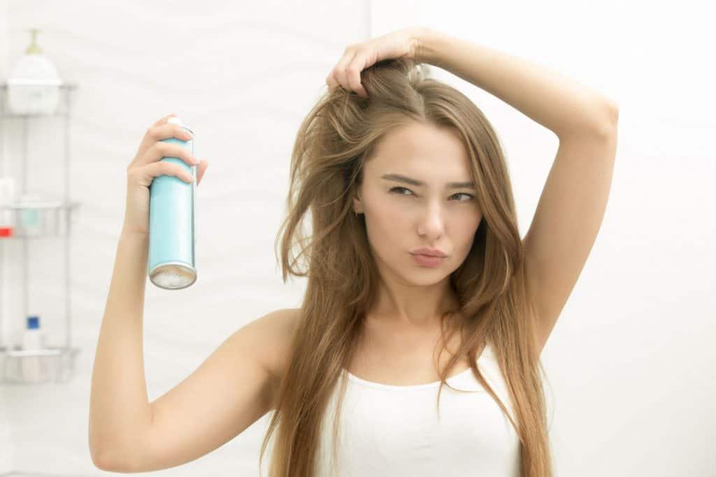 A beautiful blonde woman applying hair spray in the bathroom