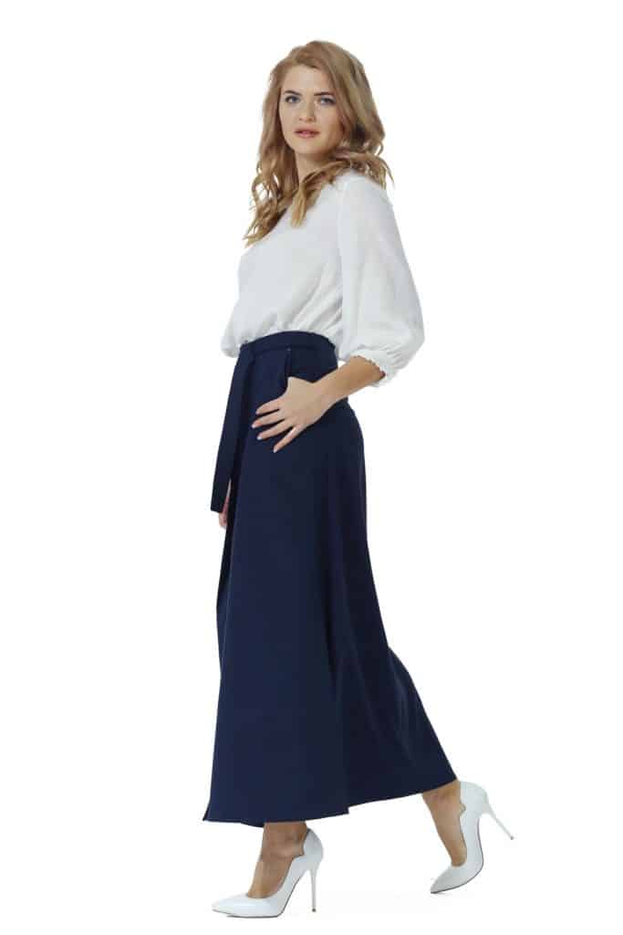 A beautiful woman wearing a white dress and a blue colored Maxi skirt on a white background