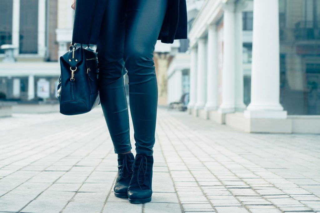 A business woman wearing a casual attire with leather pants and black boots