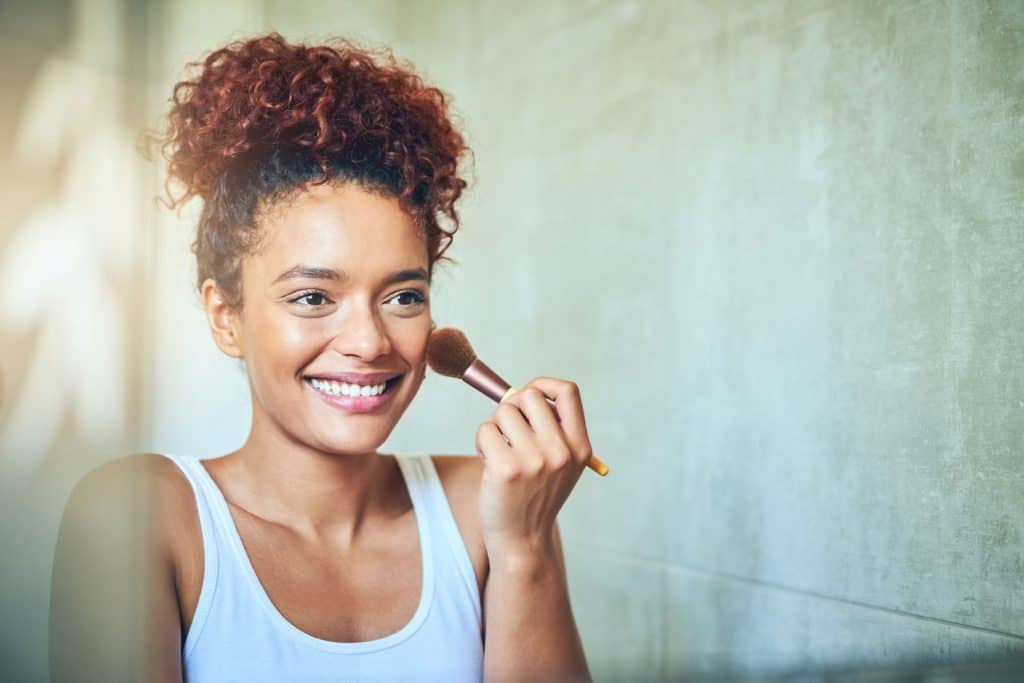 A happy woman brushing her face with highlighter