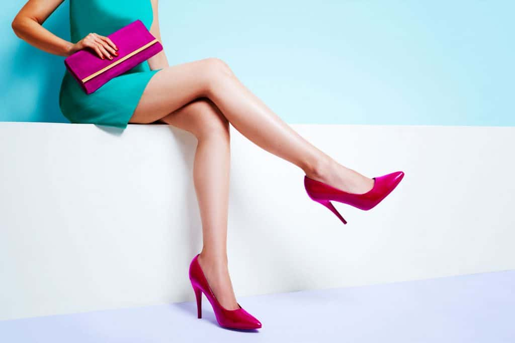 A long legged woman wearing a turquoise colored dress, a pink clutch bag, and high heeled pink shoes