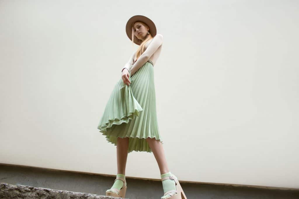 A tall beautiful woman wearing a green skirt, beige sweater, and a sun hat, How To Hem A Pleated Skirt [Even Without Sewing!]