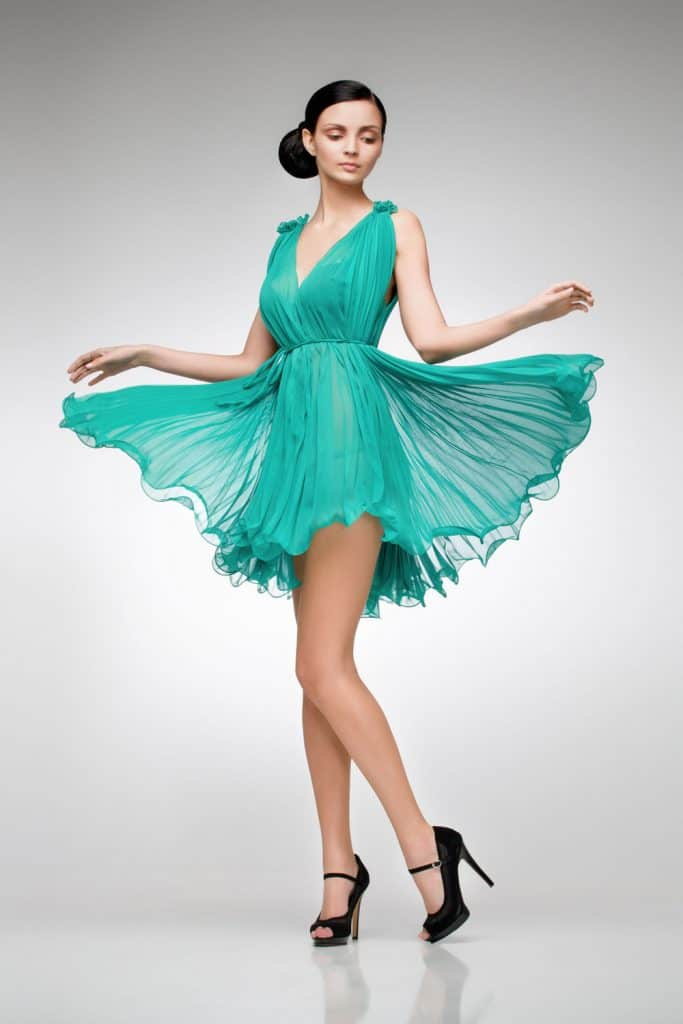 A tall beautiful woman wearing a turquoise dress and black high heeled shoes
