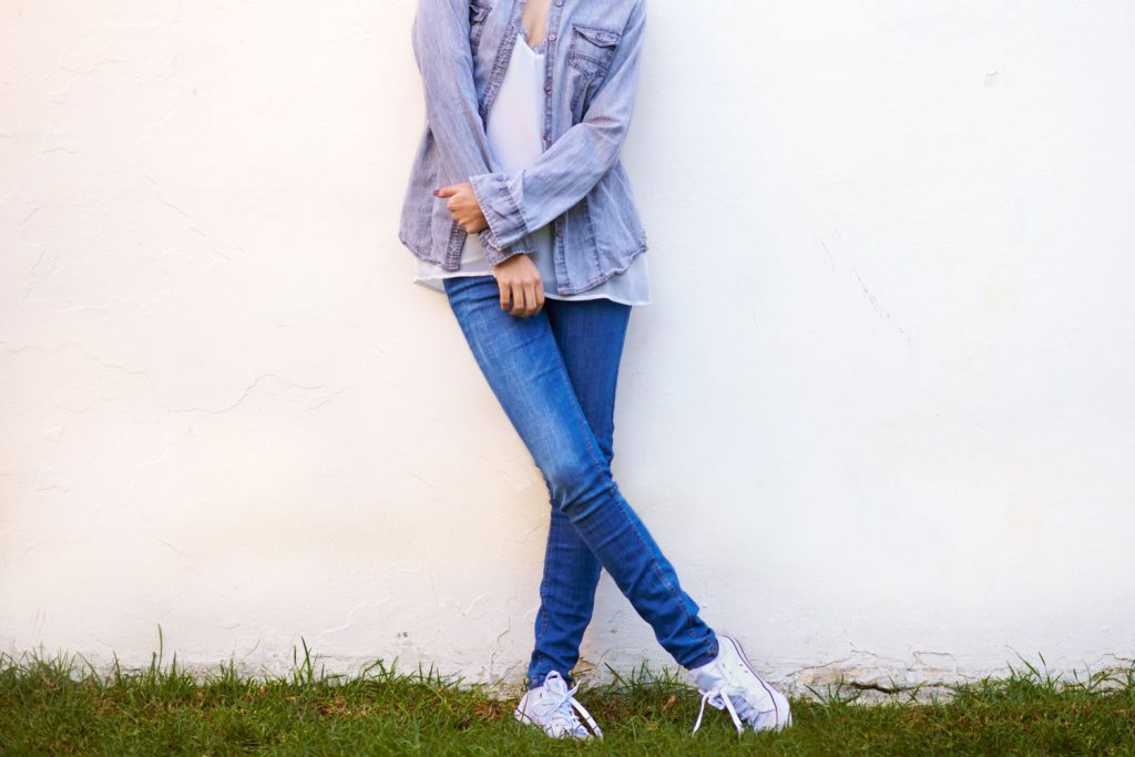 A tall beautiful woman wearing skinny jeans, white sneakers, and a denim jacket, What Sneakers To Wear With Skinny Jeans?