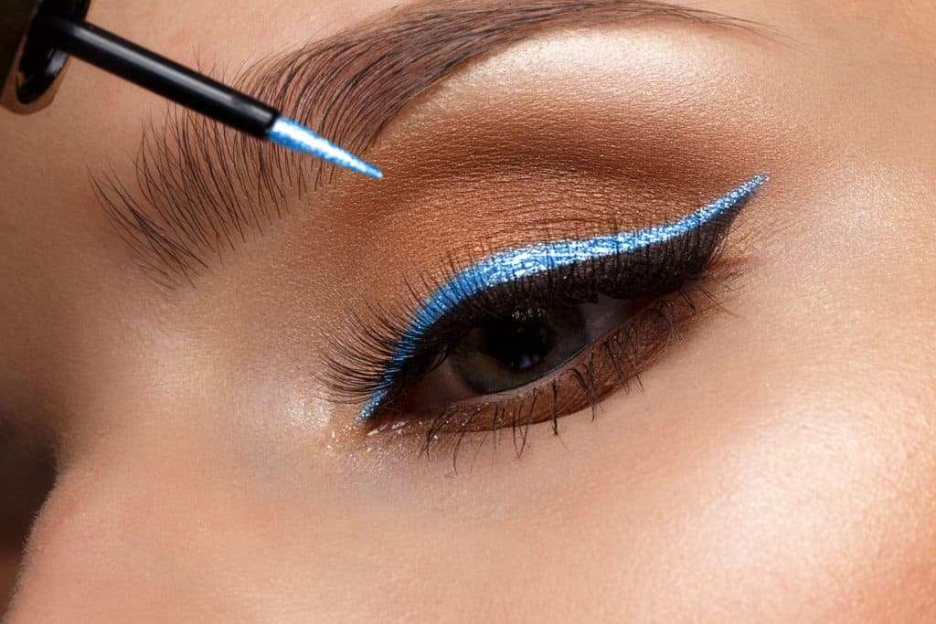 A beautiful woman applying blue glitter eyelid make