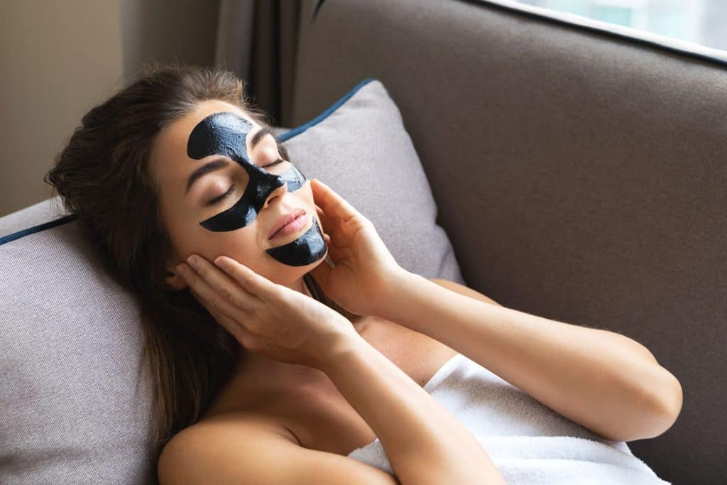 A woman applying charcoal mask on her face