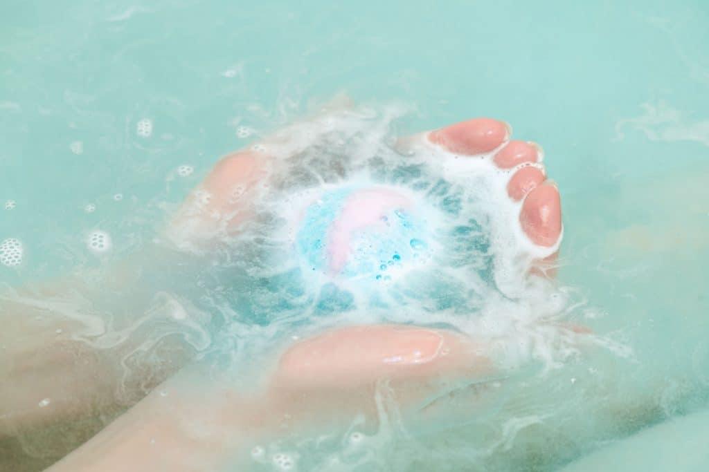 A woman dissolving a blue colored bath bomb before taking a bath