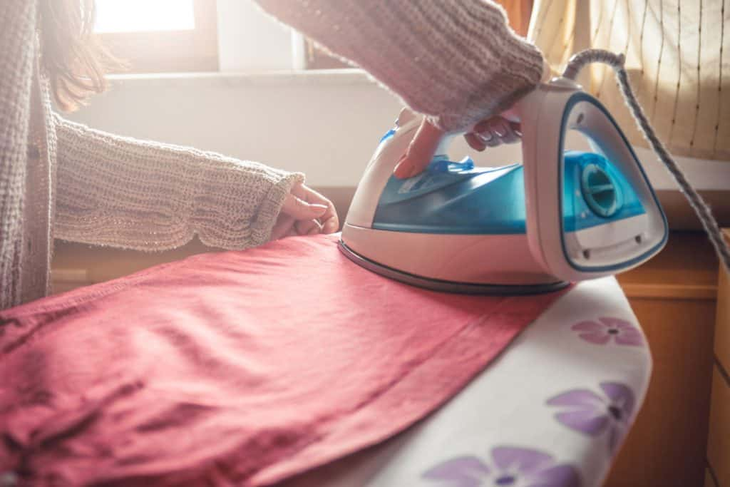A woman ironing a new cleaned skirt