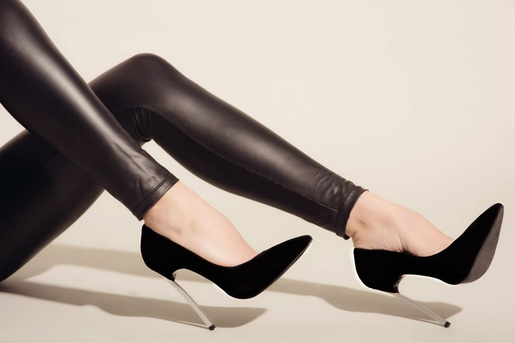 A woman posing and wearing leather pants with high heeled sandal