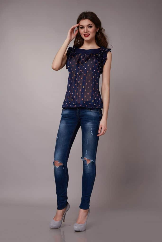 A woman posing for a photoshoot wearing a violet polka dot dress and tattered skinny jeans