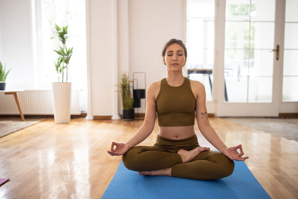 A woman wearing a yoga outfit and doing meditation on her yoga mat, How To Fold Yoga Pants And Leggings