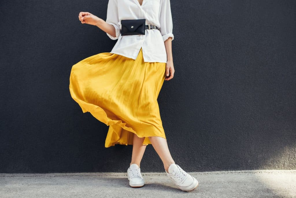 A woman wearing a white blouse and a yellow maxi skirt, Can You Wear Maxi Skirts In The Winter? [11 Outfit Ideas]